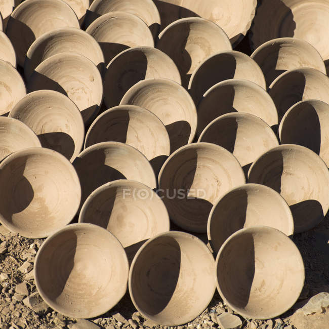 Top view of rows of clay bowls over ground — Stock Photo