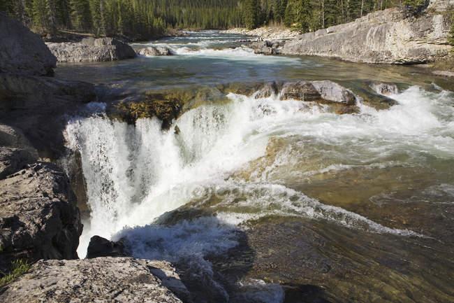 Горными водопадами и спешя реке — стоковое фото