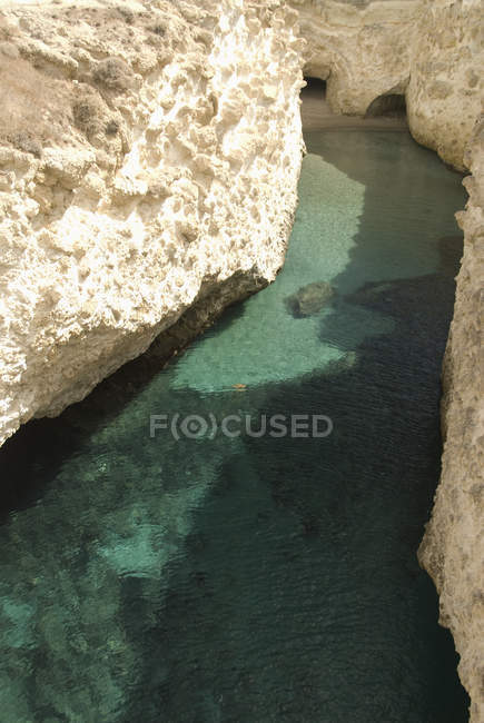 Ranquil pool of water under rock ledges — Stock Photo