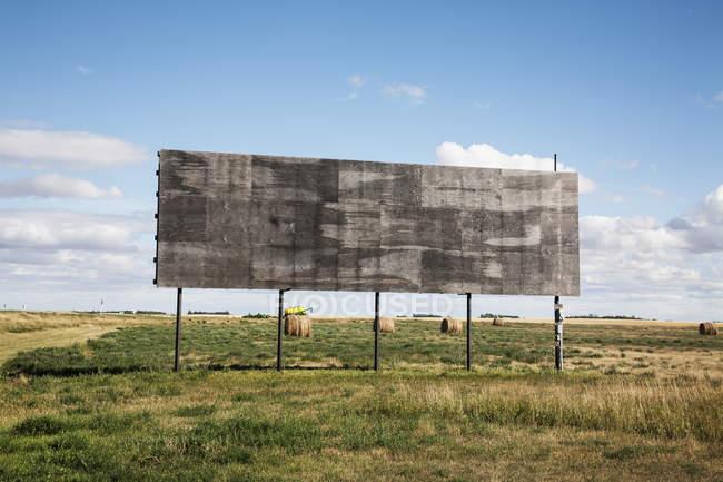 Una cartelera vacía junto a un campo de granja - foto de stock
