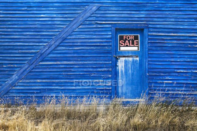 Un fienile blu con un segno in vendita — Foto stock