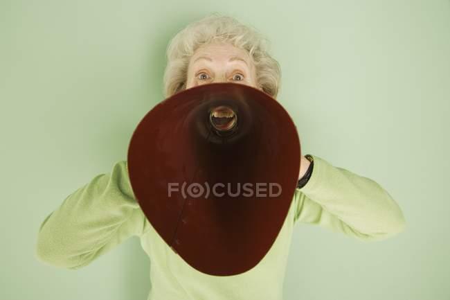 Senior caucasian woman talking into red bullhorn — Stock Photo