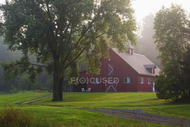 Celeiro vermelho no nevoeiro da manhã — Fotografia de Stock