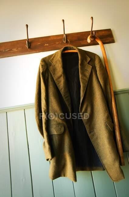 Jacke und Stock hängen an Kleiderhaken — Stockfoto