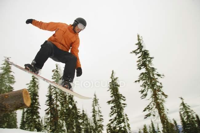 Snowboarder no ar Mid sobre neve contra árvores — Fotografia de Stock