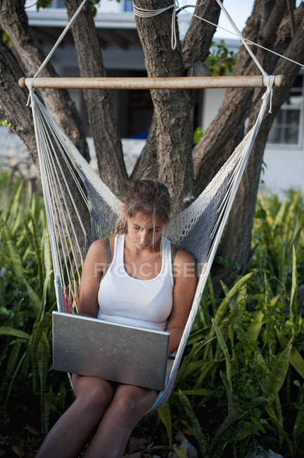 Girl Working On A Laptop While Sitting In A Hammock — Stock Photo