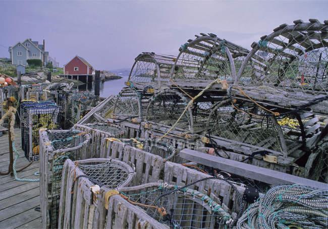 Casiers à homard en bois empilés à côté de la mer — Photo de stock