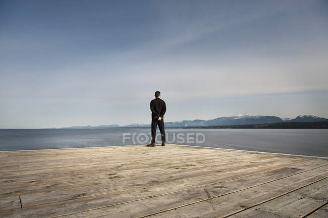 Man Stands At End Of Wooden Dock — Stock Photo