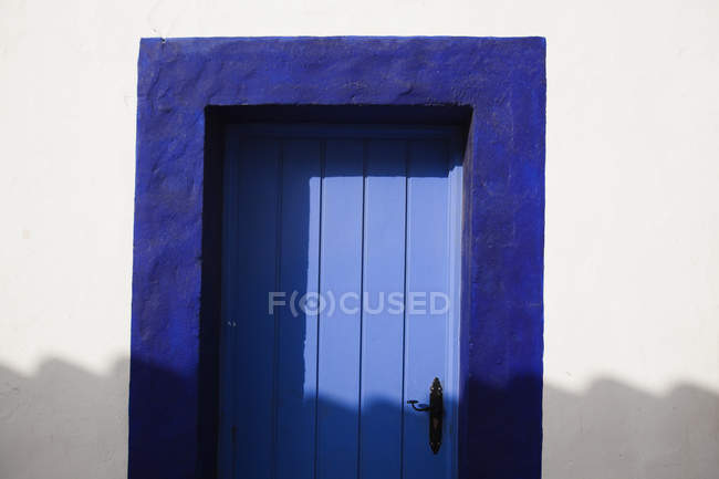 Blue Door inside white wall — Stock Photo