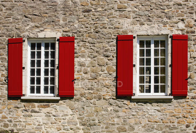Red Shutters On Windows Of Building In Lower Village Of Old Quebec City Quebec Canada