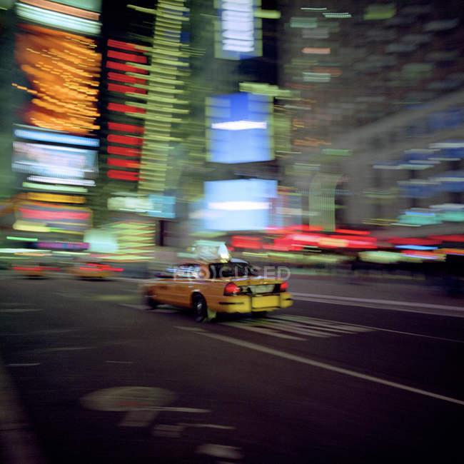 Verschwommene Taxi fahren mit Stadt Hintergrund bei Nacht, New York City, Usa — Stockfoto
