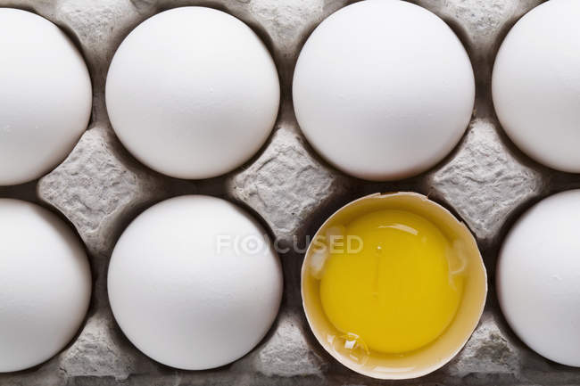White eggs in carton with one brown shelled egg open showing yoke — Stock Photo