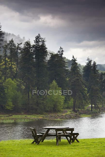 Tavola e sedie al bordo dell'acqua — Foto stock