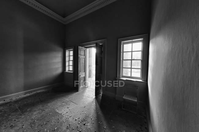 Cuarto oscuro a través de la puerta abierta - foto de stock