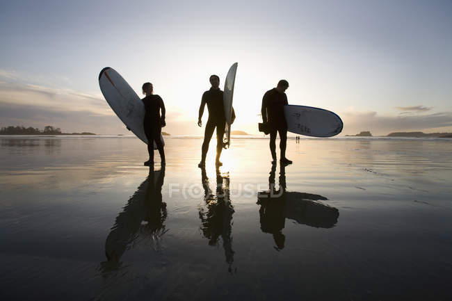 Silhouette der drei Surfer tragen Surfboards — Stockfoto