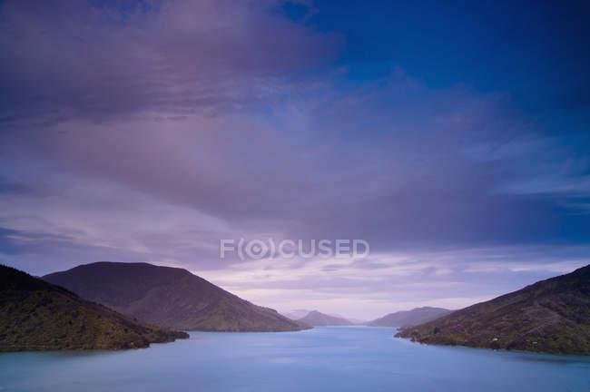 Montagnes le long de la côte sous le ciel nuageux — Photo de stock