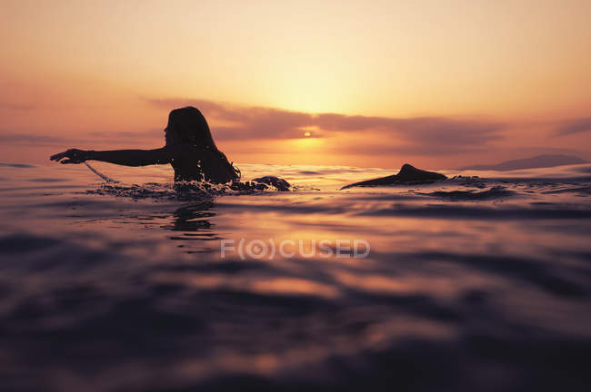 Woman laying on surfboard and watching sunset — Stock Photo