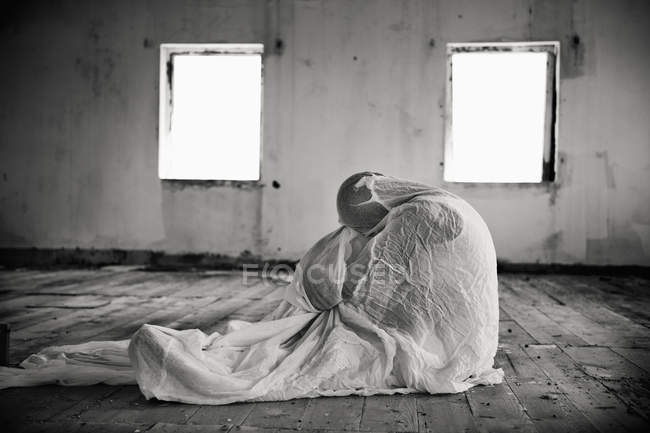Person Wrapped In Blanket In Empty Room, Monochrome — Stock Photo