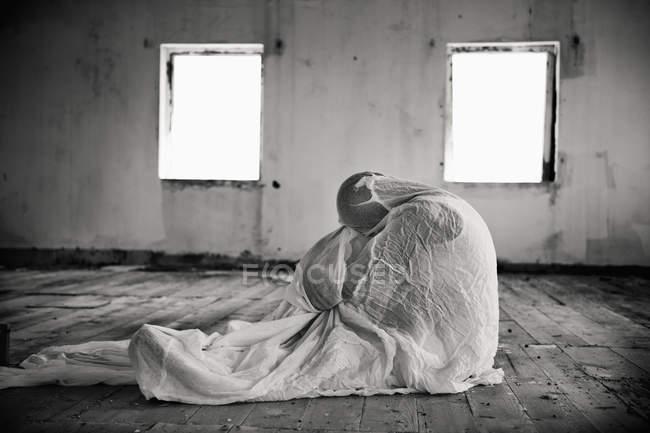 Лица, завернутый в одеяло в пустой комнате, монохромный — стоковое фото