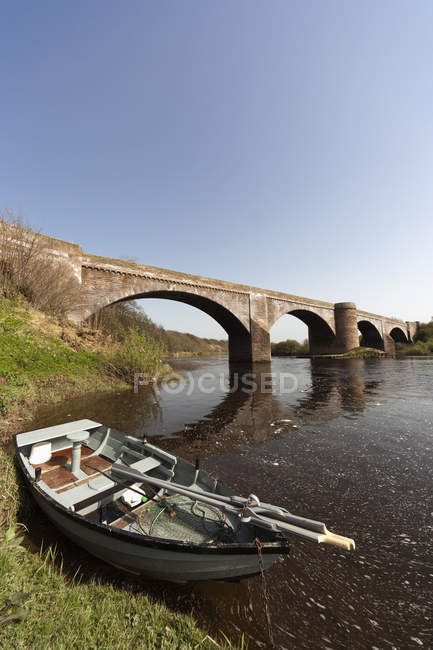 Boat Left At The Shore By A Bridge — Stock Photo