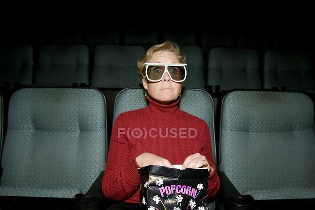 Mature woman sitting in movie theater with popcorn — Stock Photo