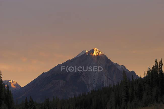 Sonnenaufgang erhellt einen Berggipfel — Stockfoto