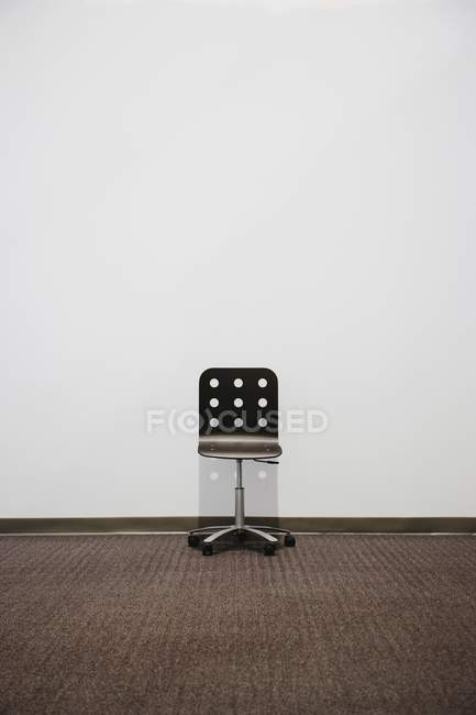 Office chair in front of white wall with copy space — Stock Photo