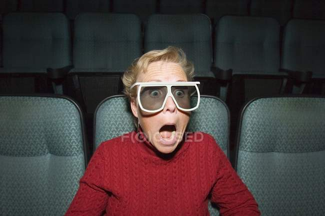 Mature woman with shocked expression at movie theater — Stock Photo