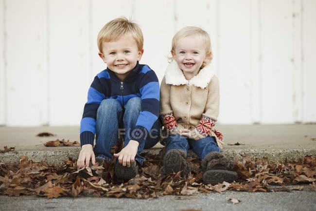 Retrato de un niño y una niña sentados entre hojas caídas de otoño - foto de stock
