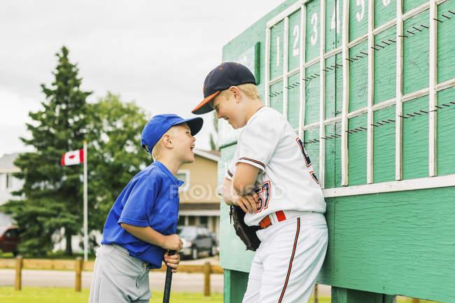 Dos niños en uniformes de béisbol discuten juguetonamente frente el  marcador durante un juego de béisbol en un campo de deportes  Fort  Mcmurray 287dae55779