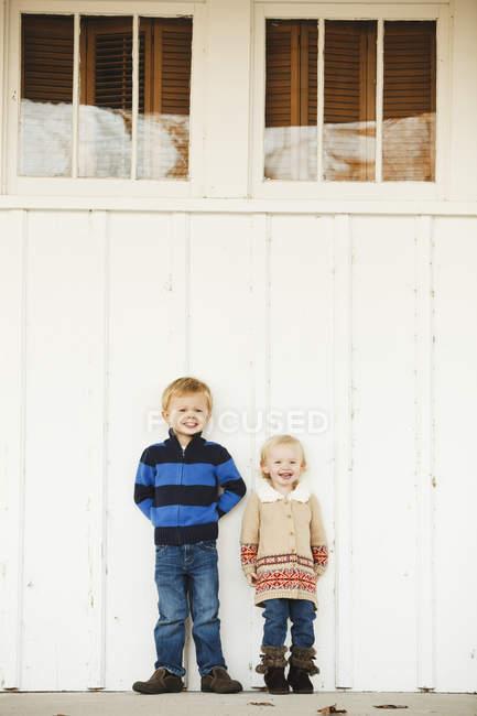 Мальчик и девочка стоят бок о бок у белой стены — стоковое фото