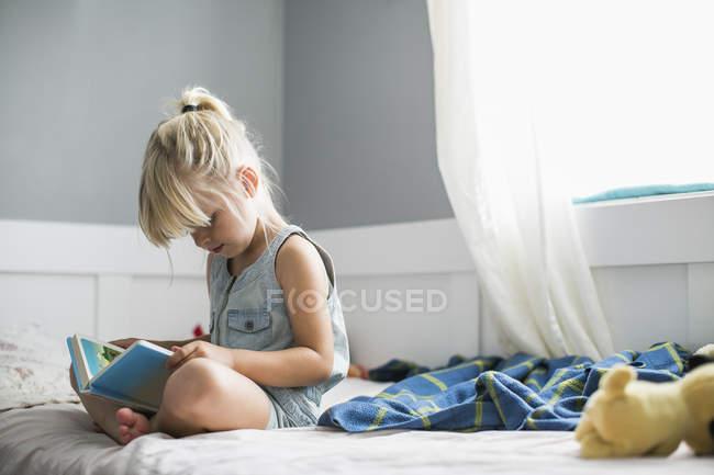 Jeune fille assise sur son lit en lisant la Bible pour enfants; Langley, Colombie-Britannique, Canada — Photo de stock