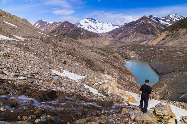 Un escursionista gazes sopra il 'intersezione' dei tre rami del ghiacciaio Castner presso Monte Silvertip rising in lontananza in Alaska Range; Alaska, Stati Uniti d'America — Foto stock