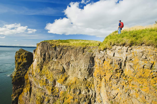Hiker looking out over ocean — Stock Photo