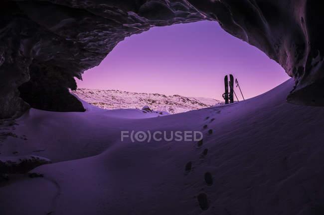 Сліди призводять до splitboard розміщені на вході в крижану печеру в рамках Canwell льодовик в Алясці діапазон після заходу сонця в зимовий період, Аляска, Сполучені Штати Америки — стокове фото