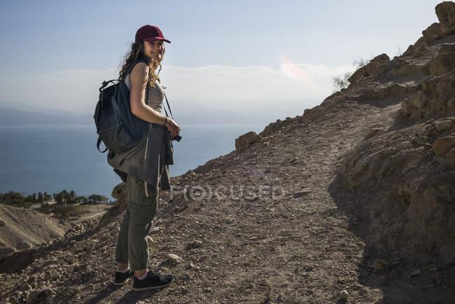 Жінка позує під час пішохідних екскурсій в Ейн-Геді, з Мертвого моря у фоновому режимі. Ізраїль — стокове фото