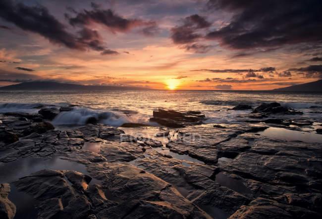 Coucher de soleil sur l'océan avec roche — Photo de stock