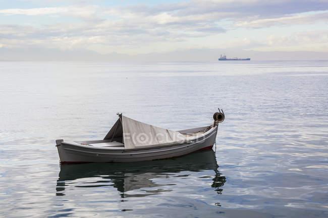 Una barca galleggiante sul tranquillo Mar Egeo con una nave nel di — Foto stock