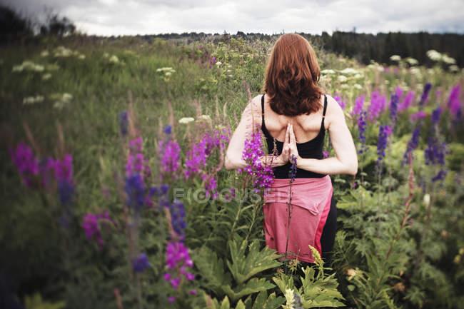Vue arrière de la femme faisant du yoga dans une prairie avec des fleurs sauvages — Photo de stock