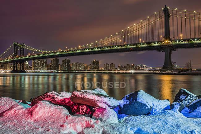 Puente de Manhattan por rocas cubiertas de nieve - foto de stock