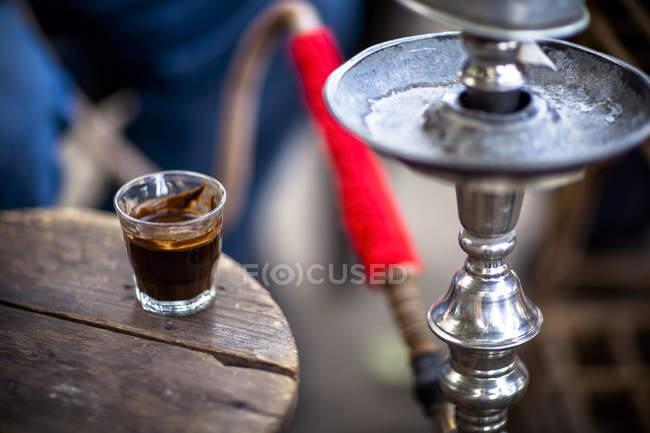 Bicchiere di caffè sul tavolo accanto sheesha, closeup — Foto stock