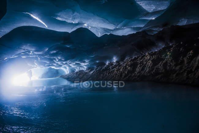 Людина за вхід до темно крижану печеру в рамках Augustana льодовик в діапазоні Аляска, Аляска, Сполучені Штати Америки — стокове фото