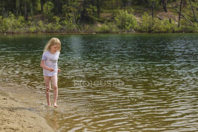 Menina brincando na água ao longo de uma praia de areia no rio na floresta — Fotografia de Stock