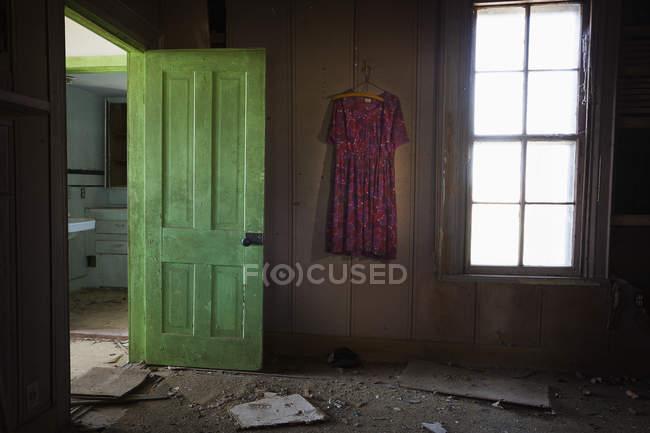 Zimmer in einem alten verlassenen Haus mit offener grüner Tür und einem alten Kleid an der Wand; Vereinigte Staaten von Amerika — Stockfoto
