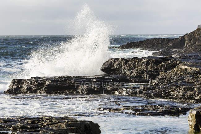 Wave crashing into rocky coast with cloudy sky — Stock Photo