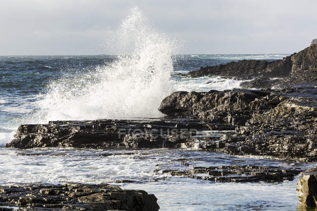 Wave crashing into rocky coast with cloudy sky — Stock Photo