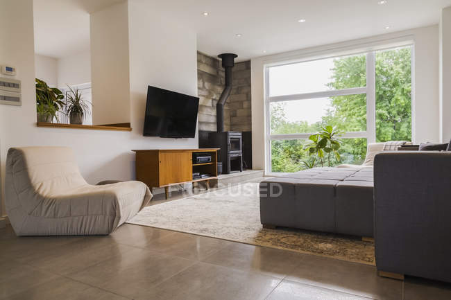 Tissu gris rembourrés sofa sectionnel et couleur crème assis des chaises dans le salon à l'intérieur d'un style moderne cube maison; Québec, Canada — Photo de stock