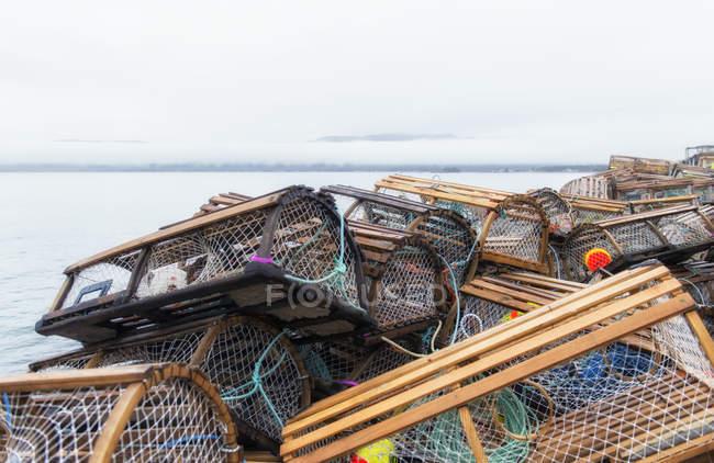 Pièges à homard empilée au hasard à côté de la mer — Photo de stock