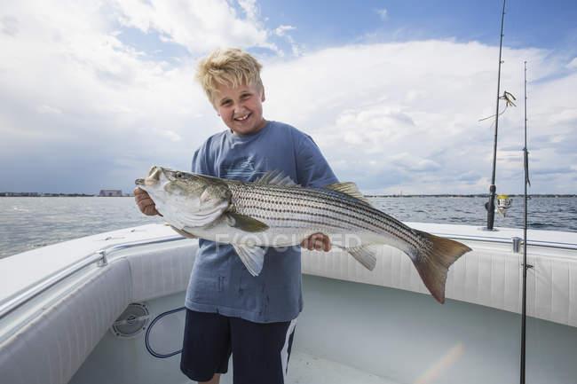 Boy holding large fish on boat of Boston harbour. Boston, Massachusetts, United States of America — Stock Photo