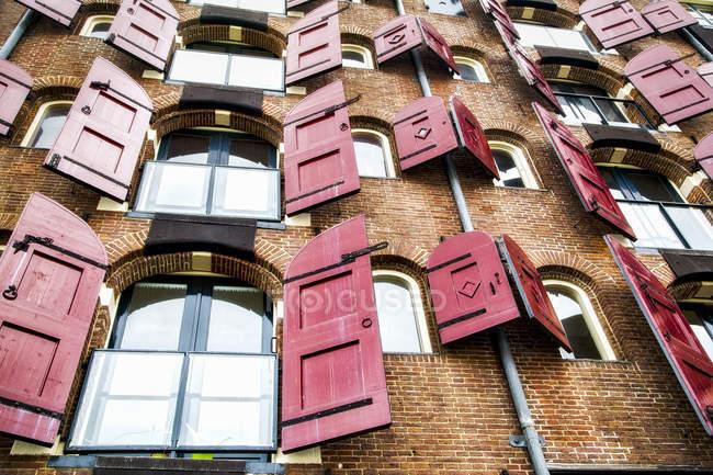 Muro di mattoni con persiane rosse aperte — Foto stock